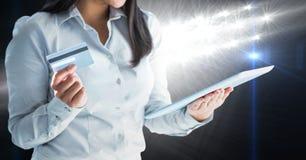 Une partie d'une femme observant un comprimé numérique examiner tenir une carte de débit photo libre de droits