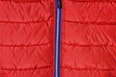 Une partie d'une veste du ` s d'hommes rouges vers le bas avec une tirette bleue Photos stock