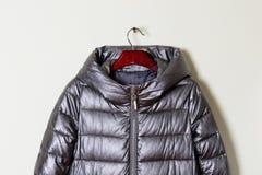 Une partie d'une veste d'hiver du ` s de femmes avec un capot gris, plan rapproché Manteau de fourrure sur un cintre, couleur mét Image libre de droits