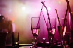 Une partie dans une boîte de nuit, verres de champagne avec des pailles Photographie stock libre de droits