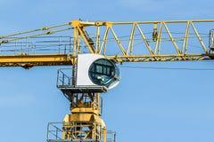 Une partie de bras jaune de grue à tour de construction contre le ciel Image stock