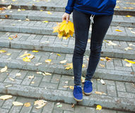 Une partie de concept pluvieux froid d'automne de personnes de corps Blues-jean et espadrilles sportives de jambes La femme dans  Images libres de droits