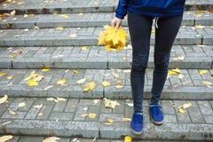 Une partie de concept pluvieux froid d'automne de personnes de corps Blues-jean et espadrilles sportives de jambes La femme dans  Image stock