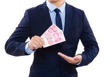 Une partie de corps d'homme d'affaires pour tenir le billet de banque chinois Photos stock