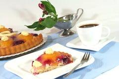 Une partie de gâteau de fruit avec une cuvette de café Image stock