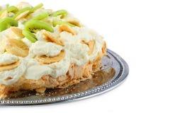 Une partie de gâteau de pavlova avec la banane et le kiwi au-dessus de réuni Photos stock