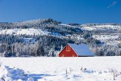 Une partie de grange rouge en hiver. Images stock