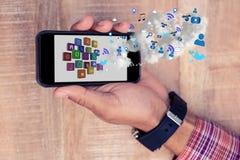 Une partie de l'homme tenant un smartphone avec les apps numériques image stock
