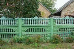 Une partie de la barrière concrète verte dans l'herbe sur la rue Image stock