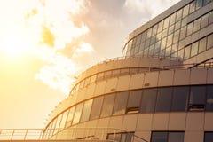 Une partie de la façade d'un bâtiment moderne est finie avec les dalles et le verre dans les rayons du coucher de soleil comme fo Images stock