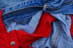 Une partie de pantalons bleus avec les poches rouges et un fer ferment à clef Images stock