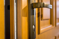 Une partie de poignée de porte en bois de porte ouverte et en métal Photographie stock libre de droits