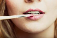 Une partie de visage Femme appliquant le rouge à lèvres rose avec la brosse Photographie stock libre de droits