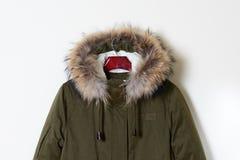 Une partie des parcs verts des vestes de la jeunesse avec un capot avec la fourrure naturelle Survêtement sur un cintre Plan rapp Photographie stock