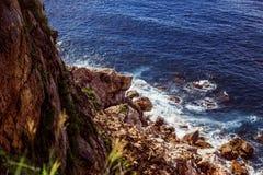 Une partie du flanc de coteau au-dessus de l'eau avec des roches autour Images libres de droits