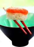 Une partie du sashimi saumoné a équilibré sur une paire de baguettes Photographie stock libre de droits