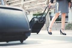 Une partie plus inférieure de femme d'affaires marchant et tirant le bagage Images libres de droits