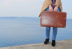 Une partie plus inférieure de girl's figurent avec la vieille valise brune sur le bord de la mer Photographie stock libre de droits