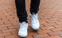 Une partie plus inférieure des jambes masculines dans des espadrilles blanches Photographie stock libre de droits