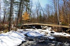 Une passerelle de pied au-dessus d'une neige a couvert le ruisseau Photographie stock libre de droits