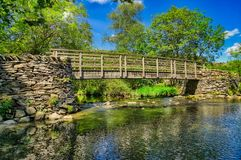 Une passerelle en bois traversant une rivière dans le secteur anglais de lac photographie stock libre de droits