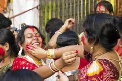 Une passionnée de femmes appliquent le sindhoor au menton d'une autre personne Images libres de droits