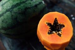 Une pastèque entière et un mensonge épluché de papaye de coupe sur une table en bois image libre de droits