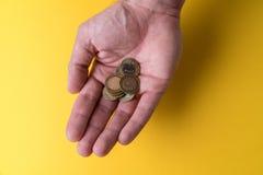 Une paume du ` s d'homme avec des pièces de monnaie Manque d'argent Faibles salaires Image libre de droits