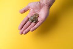 Une paume du ` s d'homme avec des pièces de monnaie Manque d'argent Faibles salaires Image stock