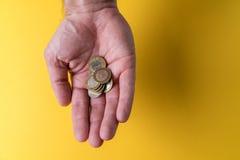Une paume du ` s d'homme avec des pièces de monnaie Manque d'argent Faibles salaires Photographie stock
