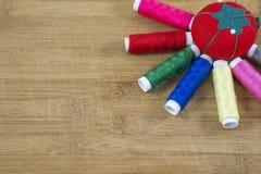 Une pelote à épingles rouge et plusieurs fils colorés comme soleil Photo stock