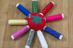Une pelote à épingles rouge et plusieurs fils colorés comme soleil Photographie stock