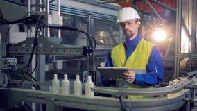 Une personne dactylographie sur un comprimé tout en vérifiant le travail du convoyeur d'usine banque de vidéos
