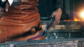 Une personne frappe l'objet en métal, le formant avec un marteau à une forge clips vidéos