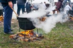 Une personne inconnue prépare un aliment roumain traditionnel disposé au chaudron sur le feu ouvert photo libre de droits