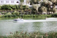 Une personne inconnue sur le ski d'eau glisse sur l'eau en bateau dans Image libre de droits