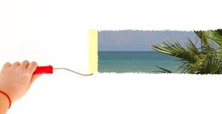 Une personne peignant un paysage d'une plage sur un mur blanc avec une brosse de rouleau Photographie stock libre de droits