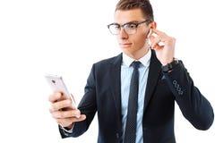 Une personne réussie, des verres de port et un costume, headph sans fil image libre de droits