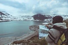 Une personne regardant la carte de trekking, le ciel dramatique le crépuscule, le lac et les montagnes neigeuses, sentiment froid Images stock