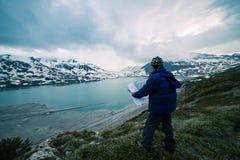 Une personne regardant la carte de trekking, le ciel dramatique le crépuscule, le lac et les montagnes neigeuses, sentiment froid Photo libre de droits