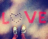 une personne se tenant au-dessus de l'amour de mot sur un trottoir Images stock
