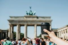 Une personne tient une tasse jetable avec du café ou une boisson différente sur le fond de la Porte de Brandebourg à Berlin photo stock