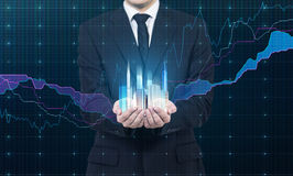 Une personne tient un hologramme des gratte-ciel comme symbole de succès financier Image stock