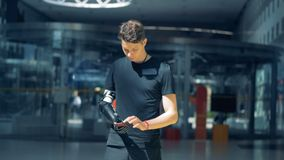 Une personne tient un téléphone avec sa prothèse cybernétique, fonctionnant avec elle Concept de cyborg banque de vidéos