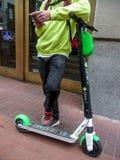 Une personne utilise leur téléphone intelligent pour louer un scooter de chaux images libres de droits