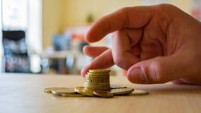 Une personne utilise ses doigts pour effleurer une pile de pièce de monnaie photo libre de droits
