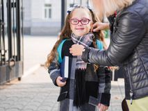 Une petite écolière dans l'uniforme avec une serviette va à l'école photo libre de droits