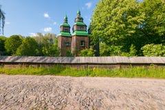 Une petite église antique avec les murs en bois avec de petites fenêtres dans elles, des tourelles et le vert a peint des dômes a Photos libres de droits