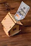 Une petite banque maison-porcine en bois et une facture d'argent de 100 dollars Photo libre de droits
