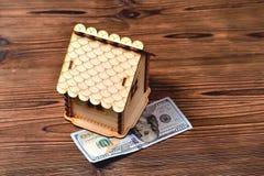 Une petite banque maison-porcine en bois et une facture d'argent de 100 dollars Images stock